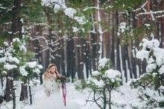 摆在与在多雪的森林冬天婚礼的花束的年轻新娘 附庸风雅 免版税库存图片
