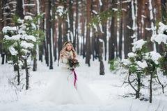 摆在与在多雪的森林冬天婚礼的花束的美丽的新娘 附庸风雅 免版税库存照片