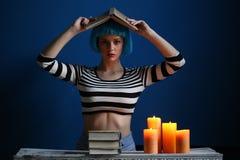 摆在与在她的头的书的女孩 关闭 可能 库存照片