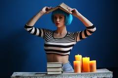 摆在与在她的头的书的蓝色假发的夫人 关闭 可能 免版税库存图片