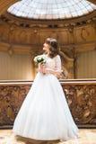 摆在与在富有的内部背景的花束的时髦的豪华新娘在老大厦的 免版税库存图片