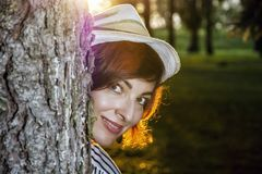 摆在与在晴朗的背后照明的树的自然妇女 库存图片