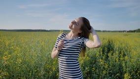 摆在与在油菜籽领域的花的女小学生 免版税库存图片