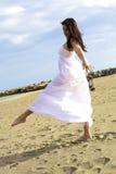 摆在与在海滩的白色礼服的舞蹈家 免版税库存照片