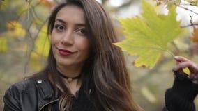 摆在与在秋季的一片干燥叶子的一名中东妇女 影视素材