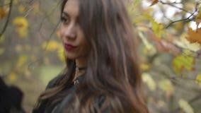摆在与在秋季的一片干燥叶子的一名中东妇女 股票视频