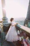 摆在与在老城堡阳台,都市风景背景的花束的美丽的红头发人新娘 免版税库存图片