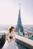 摆在与在老城堡阳台,都市风景背景的花束的美丽的红头发人新娘 库存照片