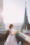 摆在与在老城堡阳台,都市风景背景的花束的美丽的红头发人新娘 免版税库存照片