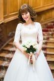 摆在与在老木台阶背景的白玫瑰花束的愉快的时髦的新娘  库存照片