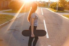 摆在与在街道上的一个滑板的美丽和时尚少妇 免版税库存照片