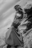 摆在与在长的礼服的岩石的时髦的女人 免版税库存照片