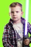 摆在与在绿色背景的激光剑的小男孩, 免版税图库摄影