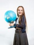 摆在与地球的愉快的女小学生反对白色背景 库存照片