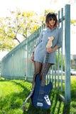 摆在与外面蓝色低音吉他的妇女 图库摄影