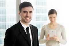 摆在与女性秘书的愉快的商业领袖 免版税图库摄影