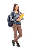 摆在与她的书的微笑的学校女孩 免版税库存图片