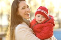 摆在与她的婴孩的母亲在冬天 图库摄影
