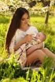 摆在与她的小逗人喜爱的婴孩的美丽的母亲在开花庭院里 免版税库存照片