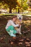 摆在与她的狗的小女孩 免版税图库摄影