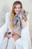 摆在与她逗人喜爱的兔子玩具的愉快的微笑的妇女画象  免版税图库摄影