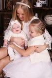 摆在与她逗人喜爱的矮小的女儿的美丽的母亲摆在圣诞树旁边 库存照片
