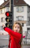 摆在与小红绿灯的逗人喜爱的小女孩 免版税库存图片