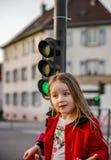 摆在与小红绿灯的逗人喜爱的小女孩 免版税图库摄影