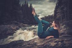 摆在与山森林的瀑布附近的美丽的妇女背景的 免版税库存照片