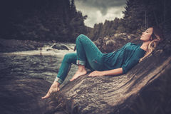 摆在与山森林的瀑布附近的美丽的妇女背景的 库存照片