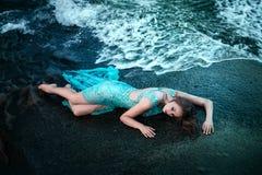 摆在与岩石的一个海滩的妇女 免版税库存图片