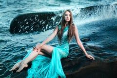 摆在与岩石的一个海滩的妇女 图库摄影