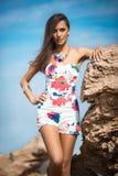 摆在与岩石的一个海滩的时髦的女人在礼服 免版税图库摄影