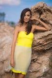 摆在与岩石的一个海滩的时髦的女人在礼服 免版税库存图片