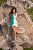 摆在与岩石的一个海滩的时髦的女人在礼服 免版税库存照片