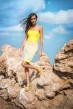 摆在与岩石的一个海滩的时髦的女人在礼服 库存图片