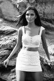 摆在与岩石的一个海滩的时髦的女人在礼服 库存照片