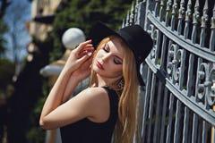摆在与帽子的时尚妇女在金属篱芭附近 库存图片