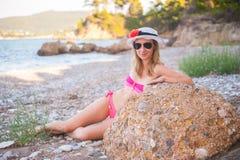 摆在与帽子的海滩的女孩 免版税库存图片