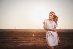 摆在与性感的神色的日落的白色礼服的美丽的妇女 库存照片