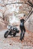 摆在与摩托车的美丽的骑自行车的人妇女户外 图库摄影