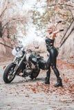 摆在与摩托车的美丽的骑自行车的人妇女户外 免版税库存照片