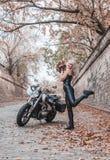 摆在与摩托车的美丽的骑自行车的人妇女户外 库存图片