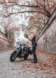 摆在与摩托车的美丽的骑自行车的人妇女户外 库存照片