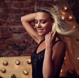 摆在与放出的年轻微笑的妇女在星和砖墙背景的长的金发 图库摄影