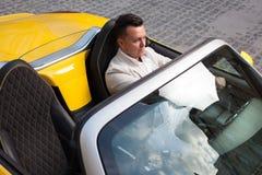 摆在与敞篷车sportcar的人 免版税库存图片