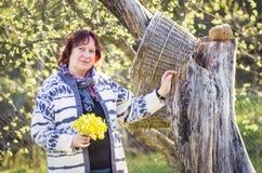 摆在与春天的树附近的妇女在手中开花 免版税图库摄影