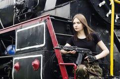 摆在与枪的女孩在引擎旁边 库存图片