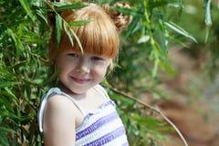 摆在与树的害羞的红发女孩 免版税库存照片