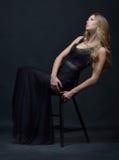 摆在与椅子的一件黑晚礼服的美丽的妇女 库存照片